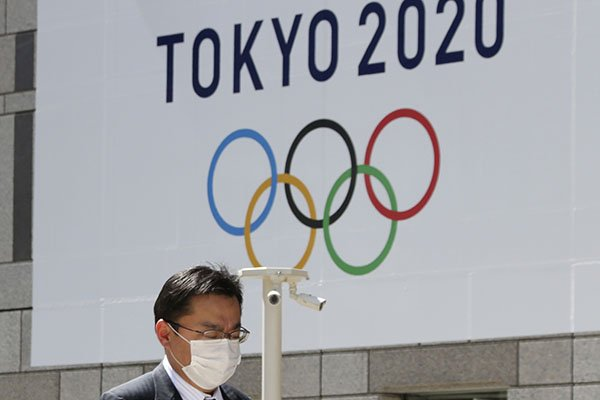 A man walks in front of a Tokyo Olympics logo at the Tokyo metropolitan government headquarters building in Tokyo, Wednesday, March 25, 2020. The Olympic torch relay was postponed Tuesday because the Tokyo Games themselves were pushed back to 2021. (AP Photo/Koji Sasahara)