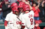 Arkansas' Casey Opitz (12) and Braydon Webb celebrate a Heston Kjerstad home run against Eastern Illinois Sunday Feb. 16. 2020 at Baum-Walker Stadium in Fayetteville. Arkansas swept the series, winning 12-3 Sunday. Both Kjerstad and Opitz will receive and extra year of eligibility if they come back to college.