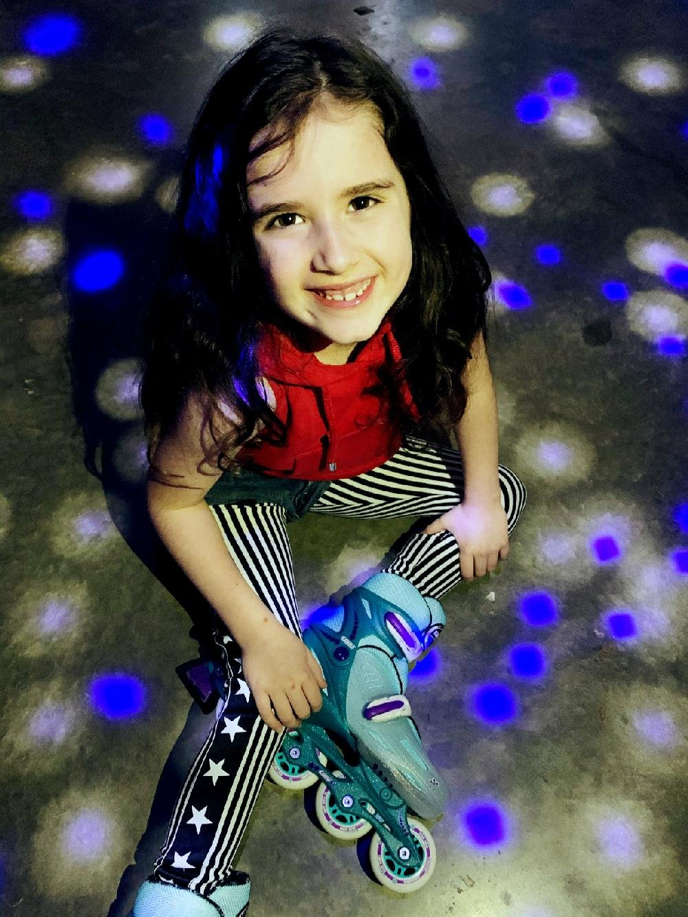 Phoenix Murphy, 7, sits on the garage floor of her Little Rock home getting ready to skate in the improvised roller rink created by her parents, Mac and Ashley Murphy. (Special to the Democrat-Gazette/Ashley Murphy)