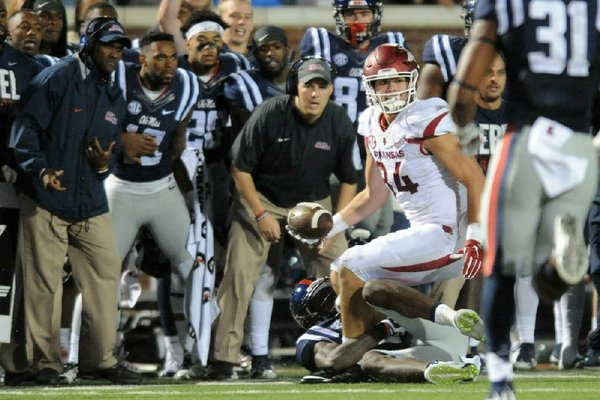 Arkansas tight end Hunter Henry prepares to lateral the ball backward as he is dragged down by Ole Miss defensive back Tony Bridges on fourth and 25 during the overtime period of the game on Nov. 7, 2015, in Oxford, Miss. Arkansas' Alex Collins scooped the lateral and converted the fourth down. The Razorbacks eventually won 53-52.  (AP photo)
