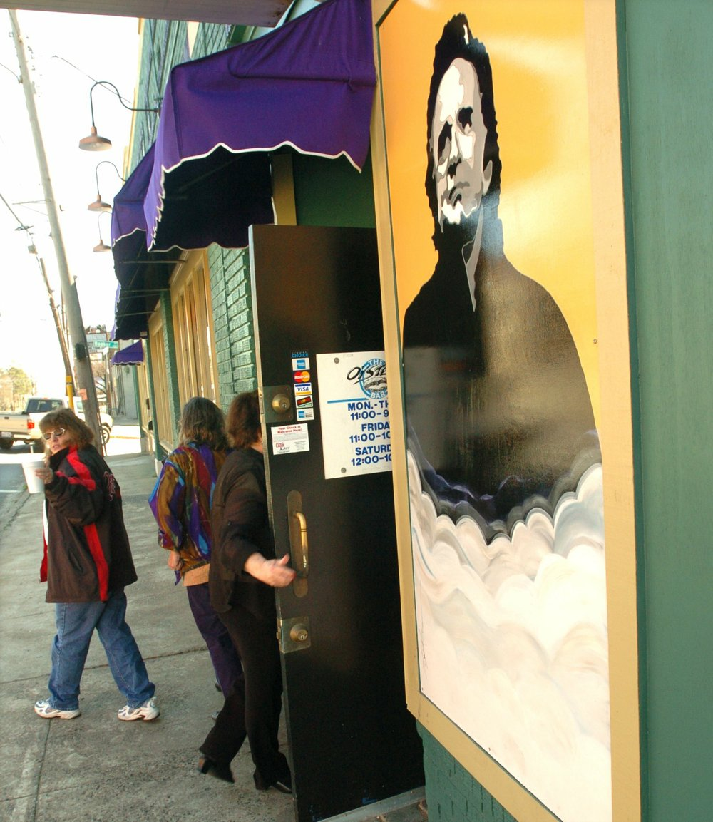 Murals, including a portrait of Johnny Cash by Stephano, a nearby business owner with cigar and bulldog by Kevin Kresse and a Tabasco bottle by Kevin Kerby, have come down off the front of The Oyster Bar on West Markham Street after more than 15 years. The windows they covered are being replaced.  (Democrat-Gazette file photos)