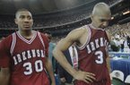 Arkansas players Corliss Williamson, right, and Scotty Thurman (30) leave the floor after losing to UCLA in the NCAA National Championship game, Monday, April 3, 1995, Seattle, Wash. UCLA won the game 89-78. (AP Photo/Eric Draper)