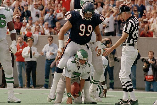 Philadelphia Eagles quarterback Ron Jaworski (7) has a Bear on his back after being sacked by Chicago Bears Dan Hampton (99) in the second quarter of the game in Chicago, Sept. 15, 1986. The Bears won 13-10 in overtime. (AP Photo/Charlie Bennett)