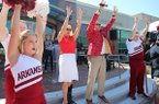 Arkansas athletics director Hunter Yurachek (second from right) and his wife Jennifer participate in the Hog Call Friday, August 31, 2018, during the ONE Hog Call event at the Town Center in downtown Fayetteville.