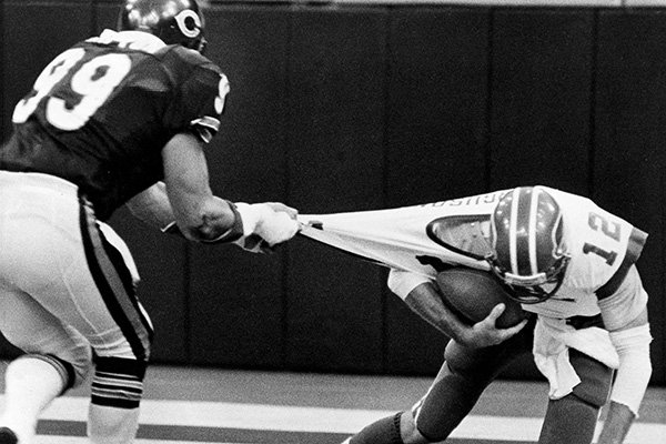 Chicago Bears defensive end Dan Hampton (99) holds on to the football jersey of Buffalo Bills quarterback Joe Ferguson, right, for a sack in the end zone during first-half action in Indianapolis, Aug. 26, 1984. (AP Photo)