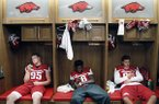 In this Aug. 9, 2015, file photo, from left to right, Arkansas' Jake Hall, La'Michael Pettway and Karl Roesler pass the time with their cell phones in the players' locker room during the annual NCAA college football media day event in Fayetteville, Ark. While autograph-signing and public appearances have been traditional ways athletes could make extra money, opportunities now are tied to social media posts where athletes could in the future be paid be paid for posting sponsored content. (AP Photo/Samantha Baker, File)