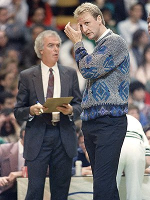 Boston Celtics superstar Larry Bird appears in street clothes near the team bench at Boston Garden at night, Friday, Nov. 18, 1988 as Celts head coach Jimmy Rodgers, left, with clipboard in hand makes some last-minute game plans prior to the start of NBA action against the Washington Bullets. (AP Photo/Elise Amendola)