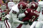 Arkansas' Marvin Jackson (3) is tackled by Oklahoma's Will Peoples during the first quarter of the Cotton Bowl Classic on Jan. 1, 2002, in Dallas.