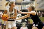 Riley Hayes (22) of Bentonville passes the ball as Claudia Bridges defends for Fayetteville at Tiger Arena in Bentonville, Ark., on Friday, February 14, 2020.