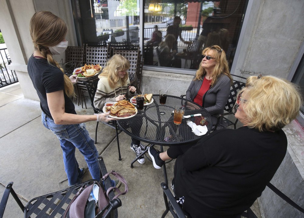 Waitress Anna Barnard (left) serves diners Ella Rena (seated left), her mother Louise Hope (center) and April Smith Monday on the patio at Dugan's Pub in downtown Little Rock.  (Arkansas Democrat-Gazette/Staton Breidenthal)