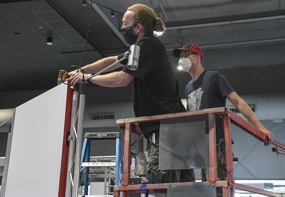 """Exhibit technician Ben Wilkins, left, and Director of Exhibits Dylan Kuchel work on a section of """"Bionic Me"""" Wednesday at Mid-America Science Museum. The exhibit opens today. - Photo by Grace Brown of The Sentinel-Record"""